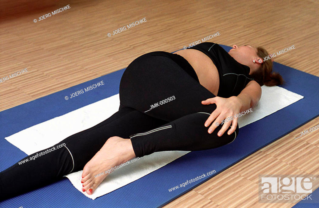 Stock Photo: Young woman at the gym, fitness center, doing some gymnastics on a mat, streching.