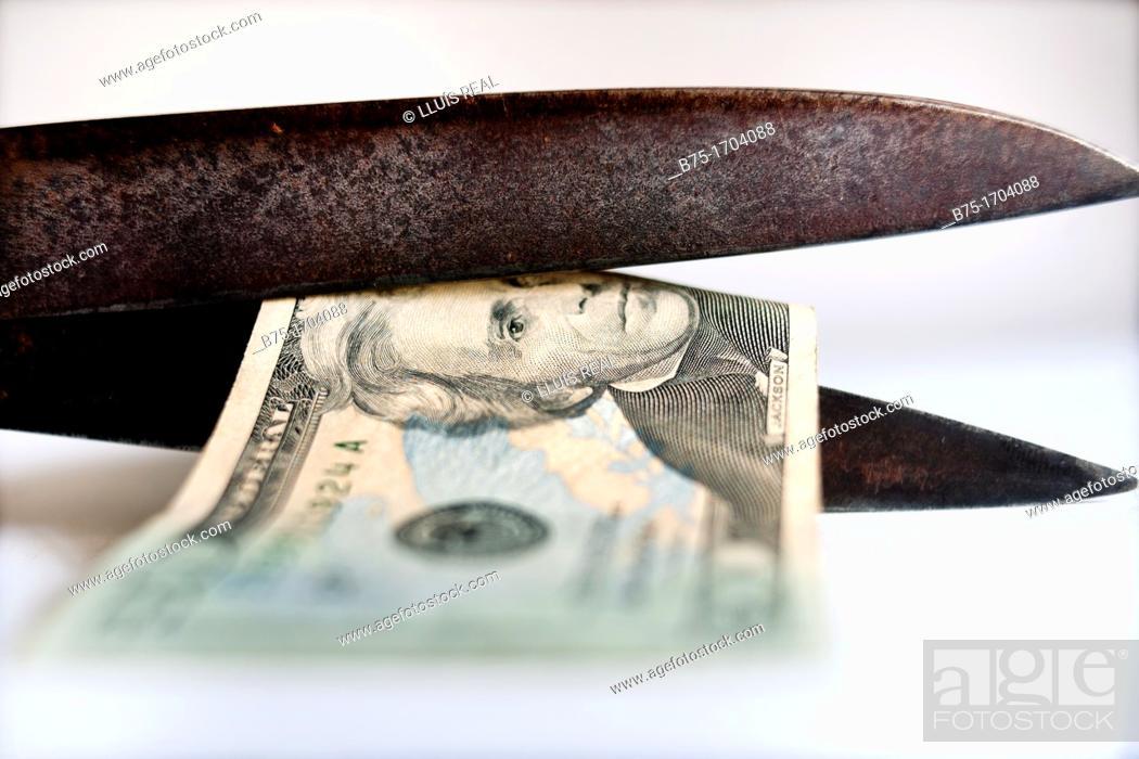 tijeras cortando un billete de 20 dolares, recortes economicos
