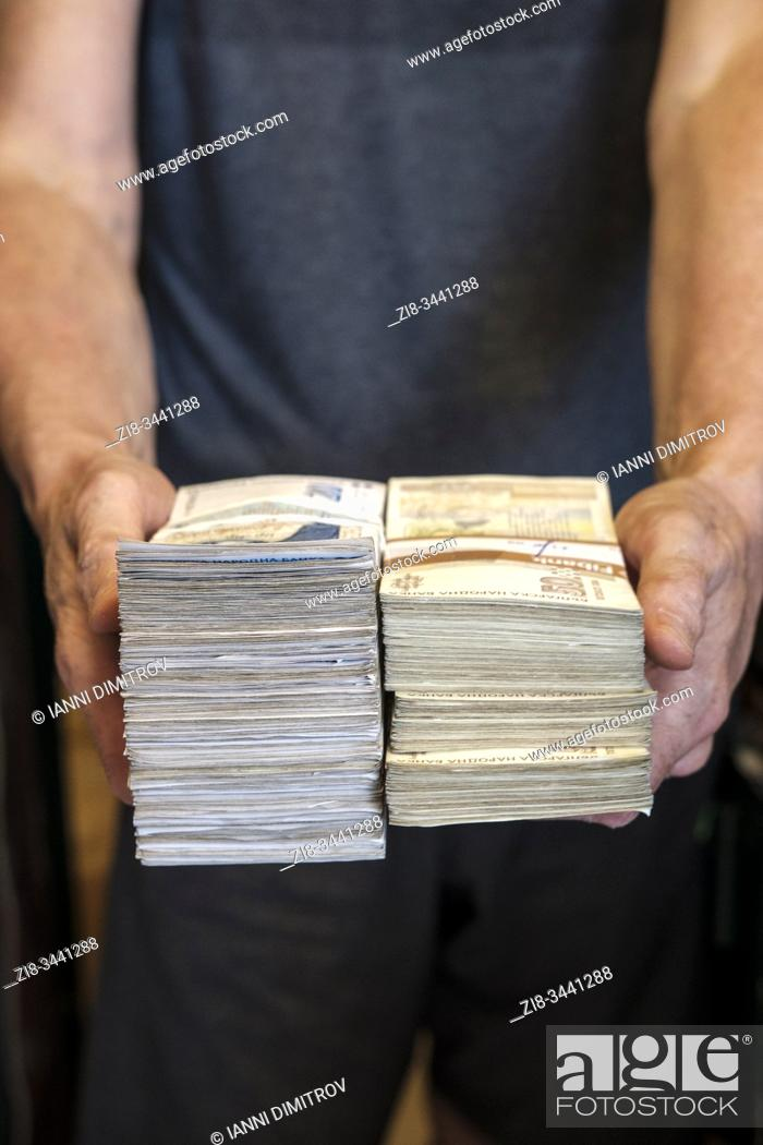 Stock Photo: Man holds wads of cash. Bulgarian currency, Bulgarian lev.