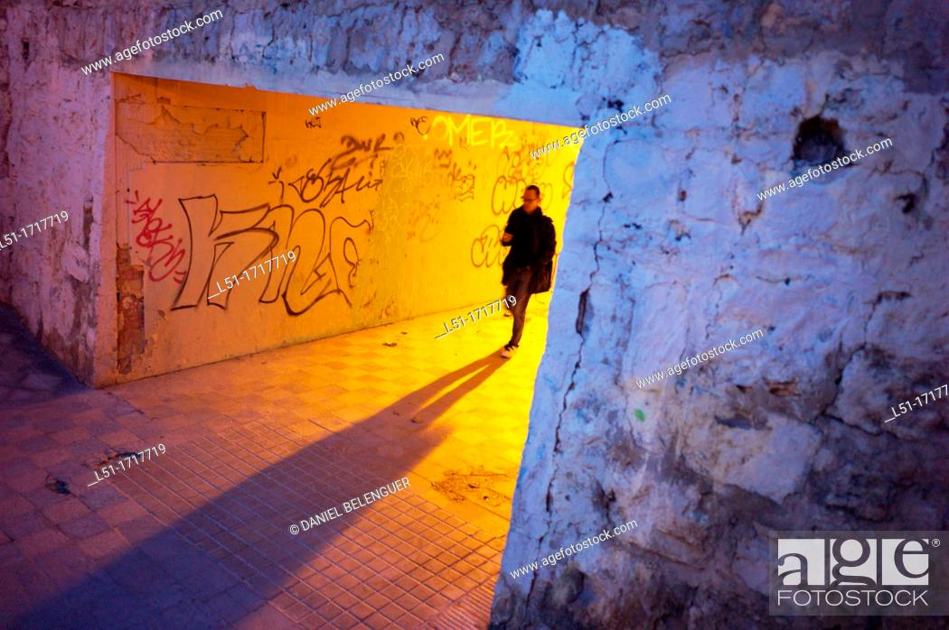 Stock Photo: Young man walking through a tunnel at dusk, Valencia city, valencia, Spain.