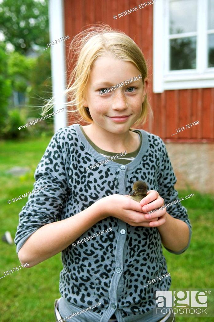 Stock Photo: Young girl with baby duck on her hand.