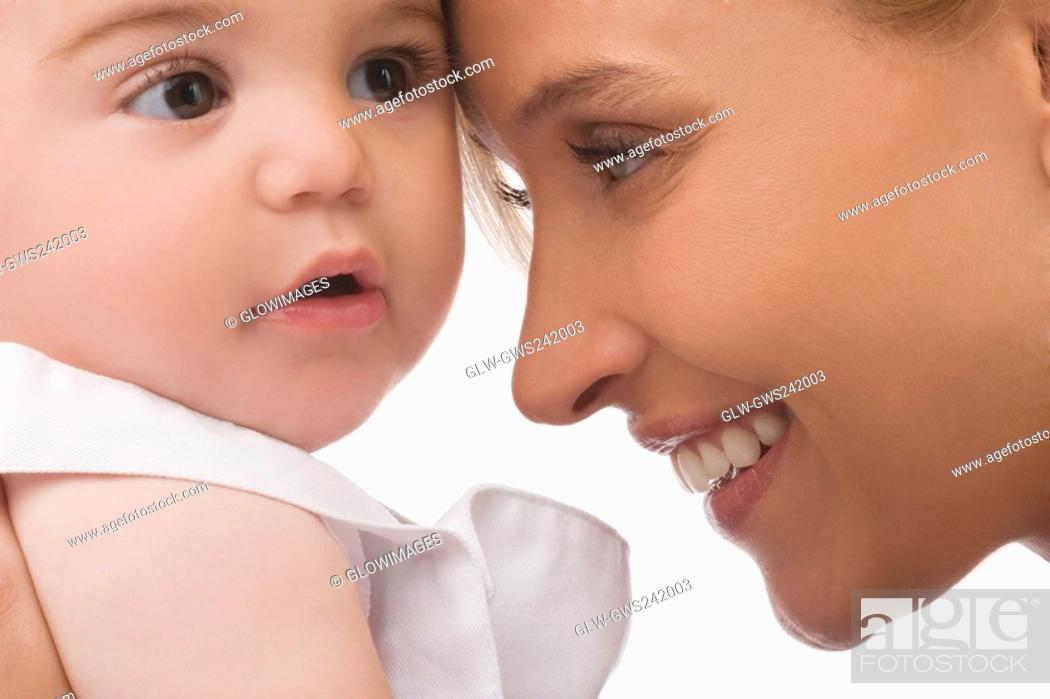 Stock Photo: Close-up of a mid adult woman smiling with her son.