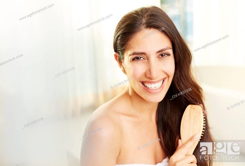 Imagen: Portrait smiling brunette woman brushing hair.
