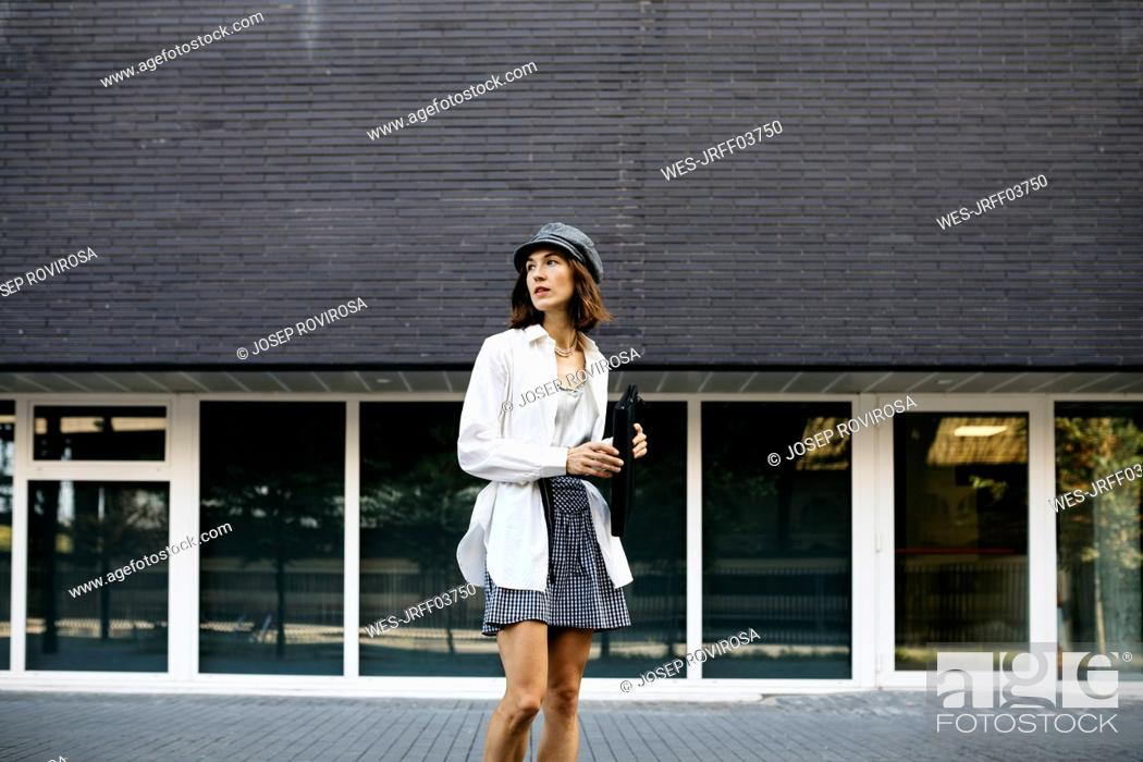 Stock Photo: Pretty woman, carrying folder, commuting in the city.