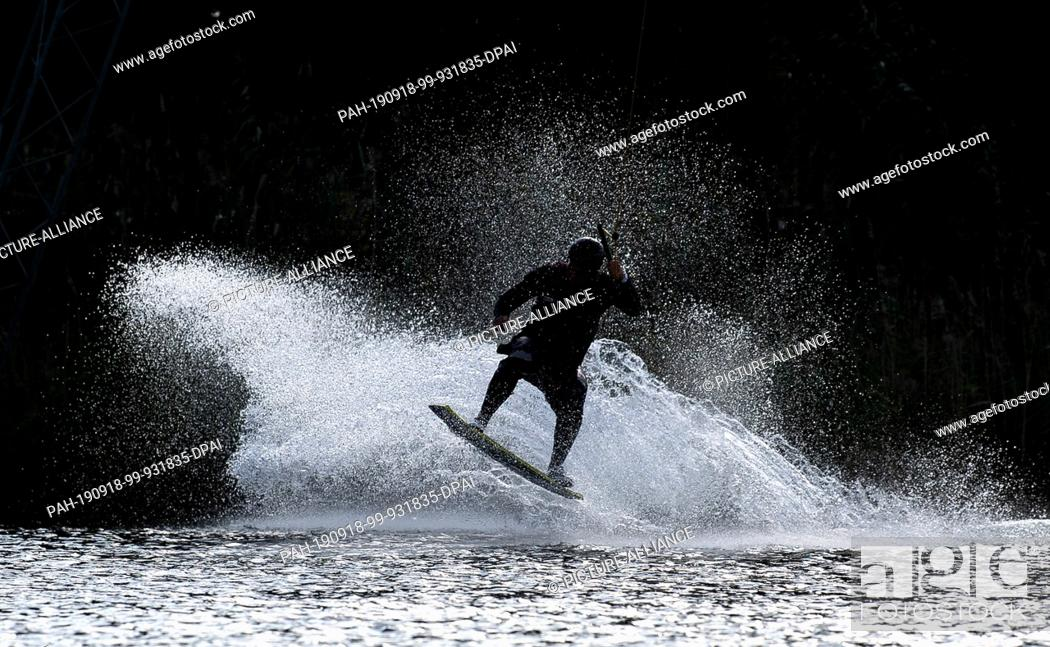 Stock Photo: 18 September 2019, Lower Saxony, Wolfsburg: Water splashes as a wakeboarder on a water ski facility drives through a bend. Photo: Sina Schuldt/dpa.