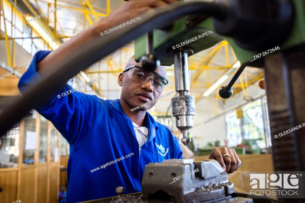 Stock Photo: Fitting and Turning Trade of the Windhoek Vocational Training Centre, Namibia. Student works with a drill machine making holes through a piece of steel.