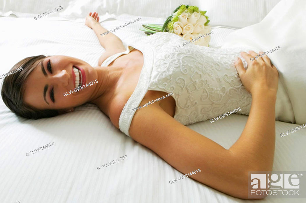 Stock Photo: High angle view of a bride lying on the bed and smiling.