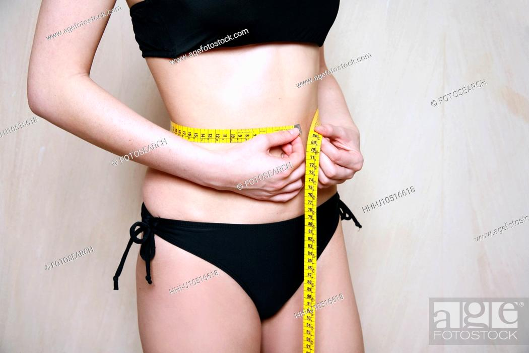 Stock Photo: Woman measuring her waist.