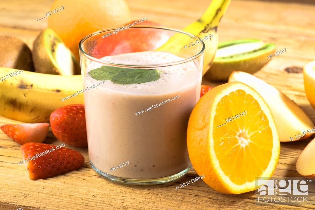 Photo de stock: Natural banana smoothie surrounded by fruit on wooden base.