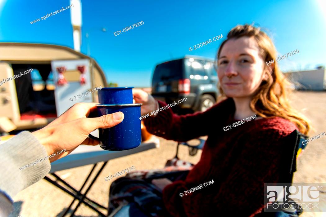 Stock Photo: Selective focus of two adult persons drinking a cup of coffee or tea while sitting outside in front of their caravan camper.