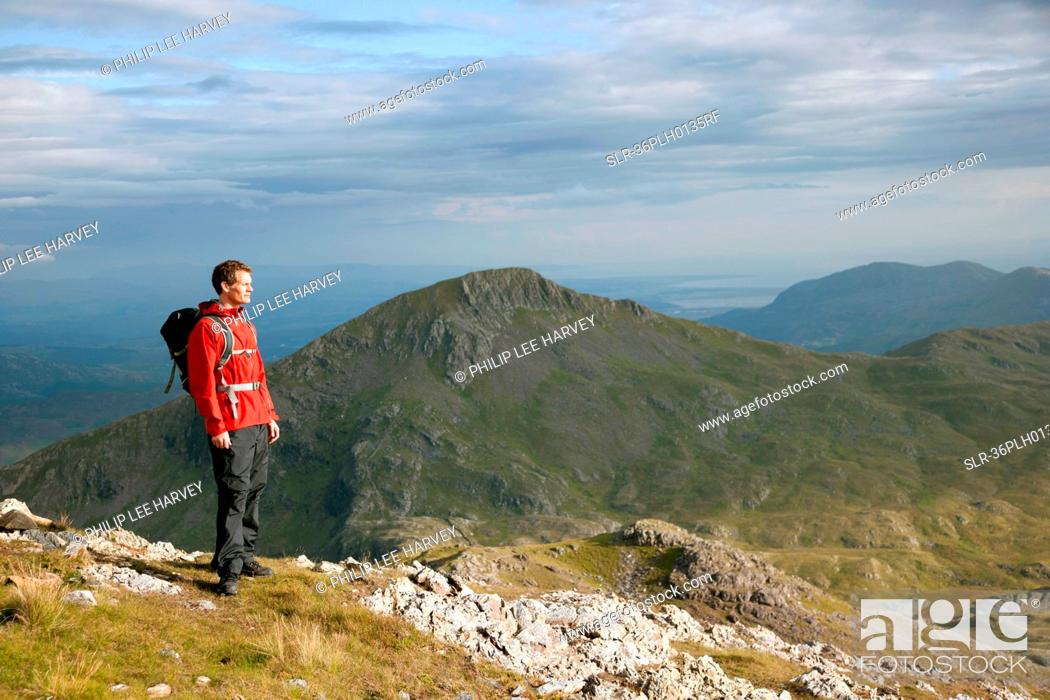 Stock Photo: Hiker overlooking view from mountaintop.