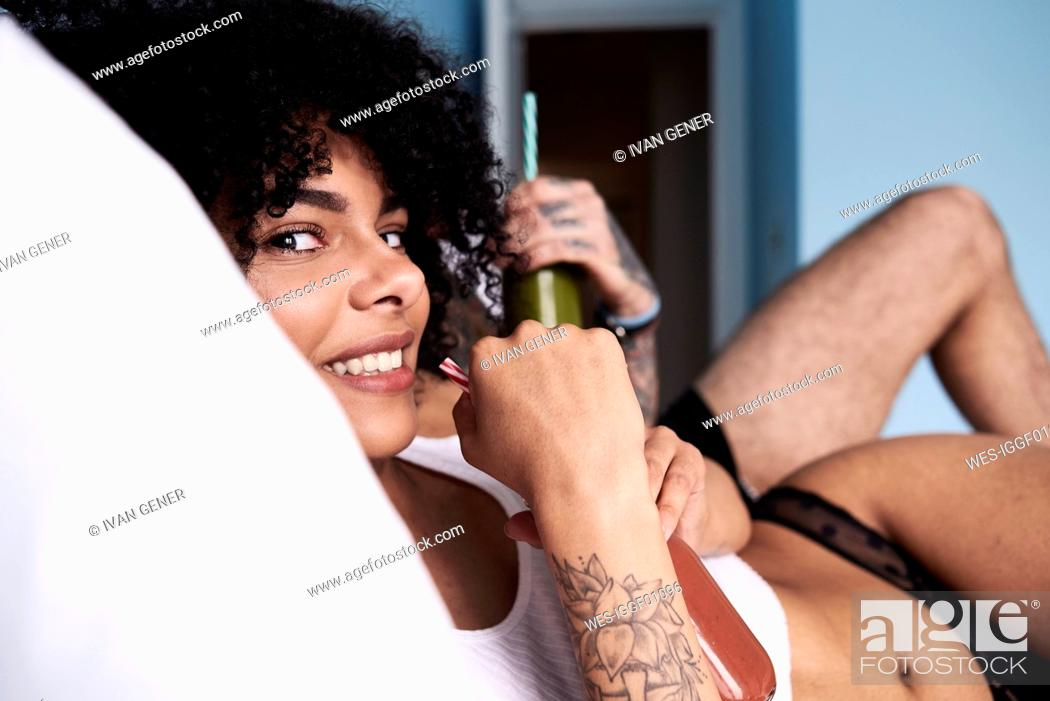 Stock Photo: Portrait of smiling young woman with boyfriend lying in bed drinking smoothie.