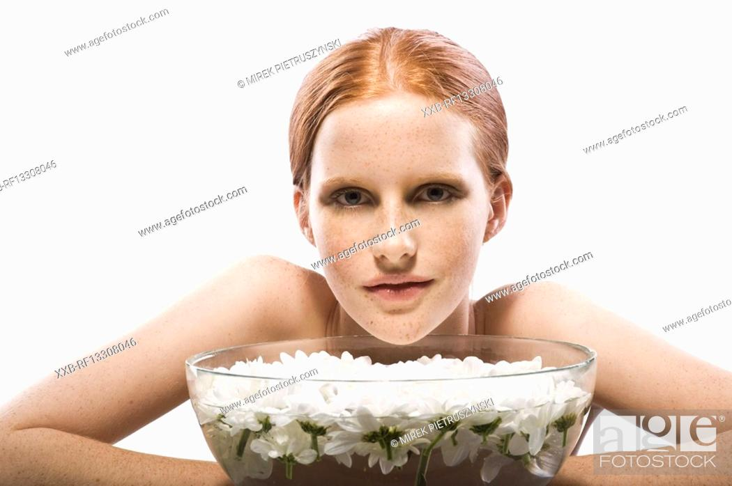 Stock Photo: young woman with bowl full of water and flowers.