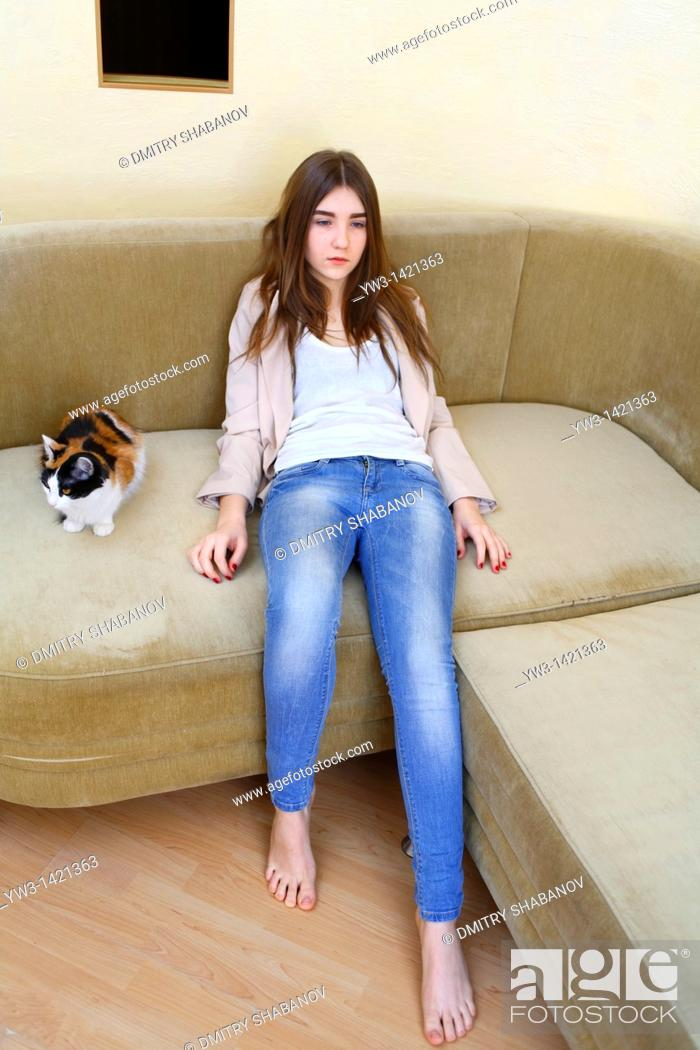 Stock Photo: Portrait of a young blond woman in jeans lying on sofa.