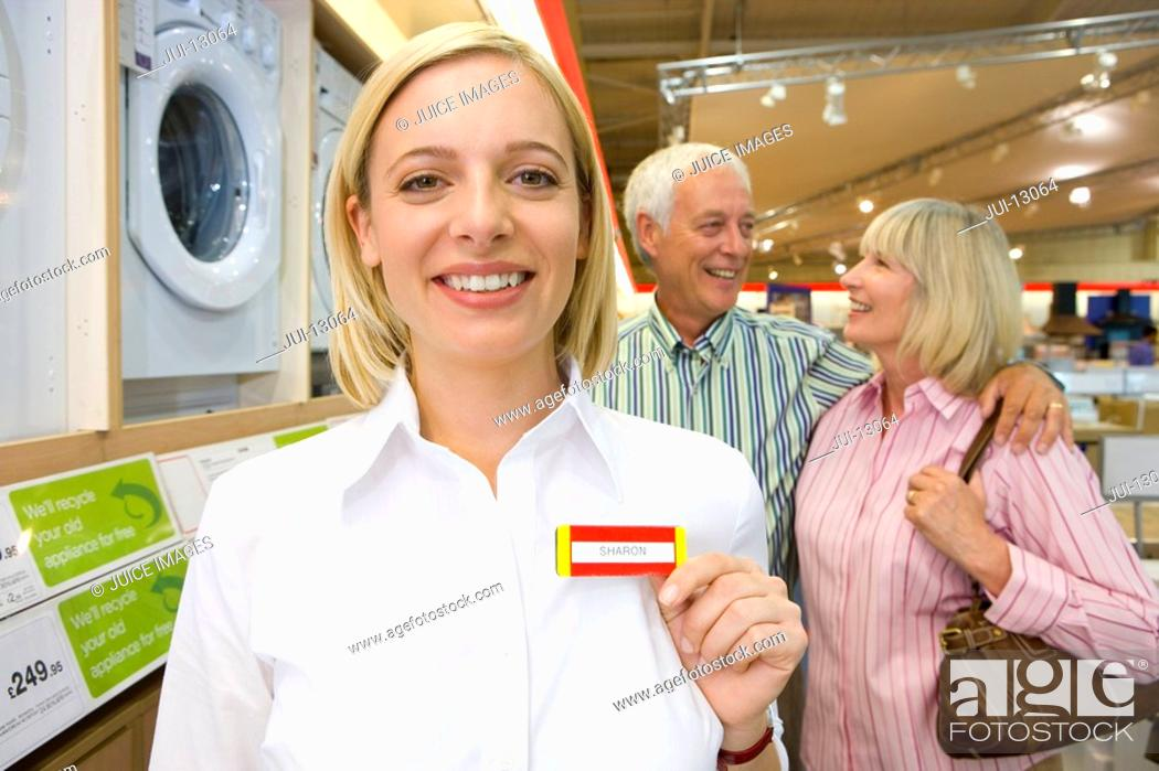 Stock Photo: Shop assistant with hand to name badge by mature couple, smiling, portrait.