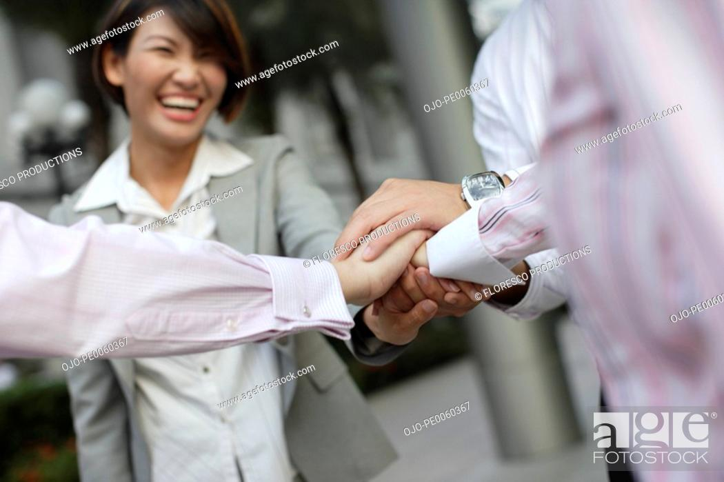 Stock Photo: Four businesspeople outdoors with hands together in circle.