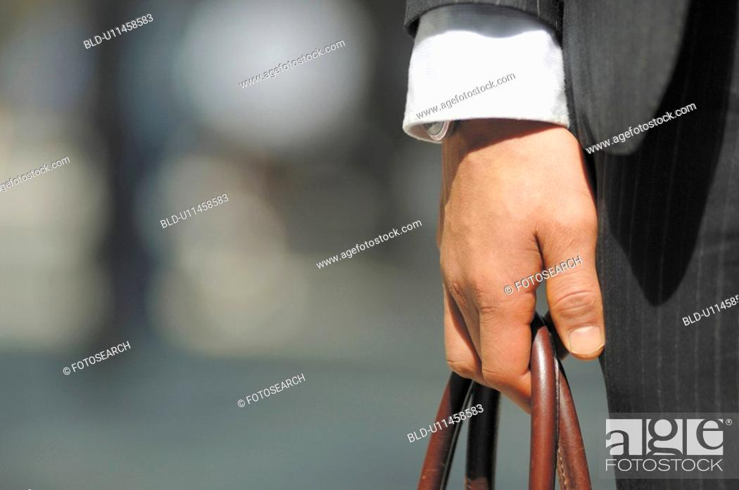 Stock Photo: Hand of the businessman with the bag.