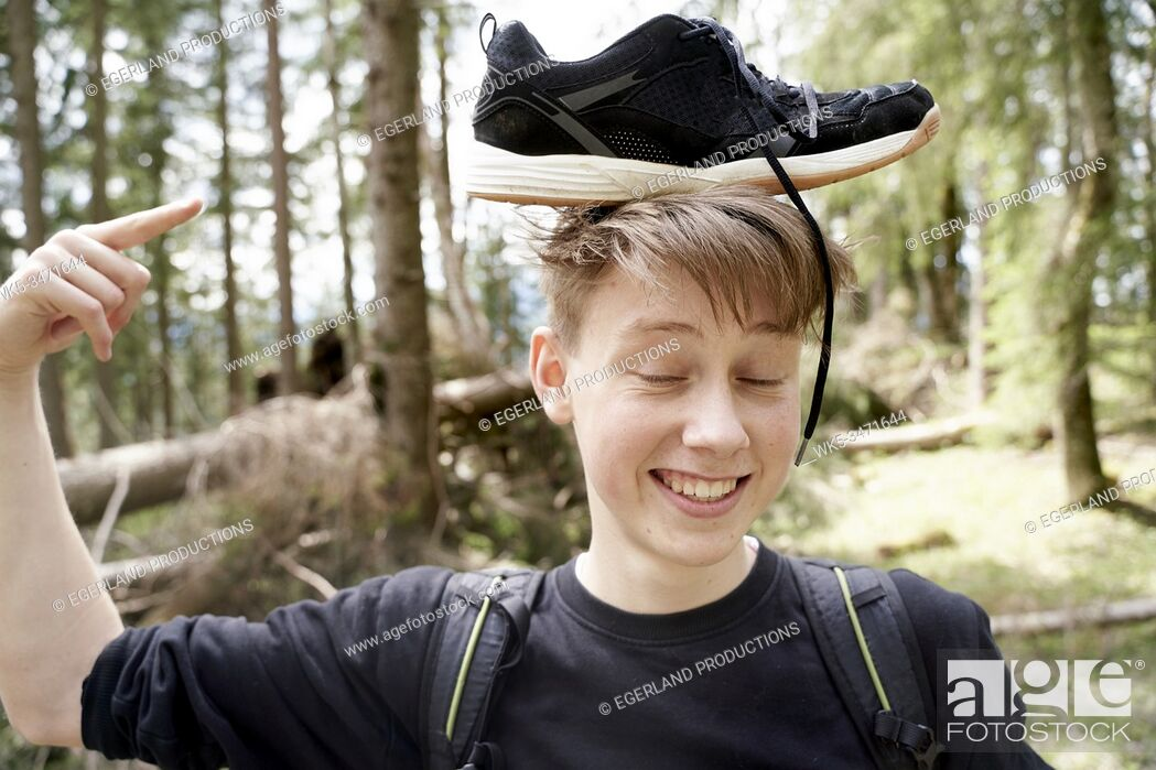 Imagen: Young boy in forest with sneaker on his head. Bad Tölz, Upper bavaria, Germany.