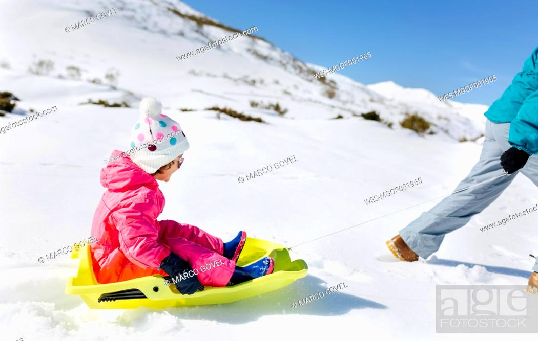 Stock Photo: Girl sitting on sledge, mother pulling.