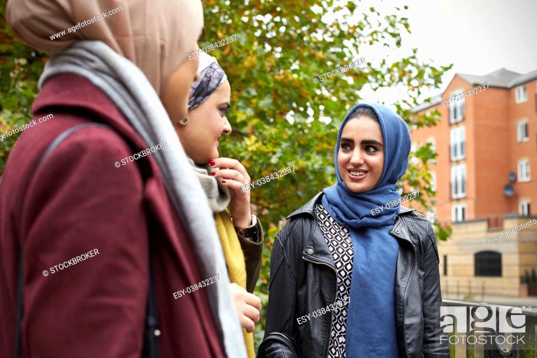 Stock Photo: British Muslim Female Friends Meeting In Urban Environment.