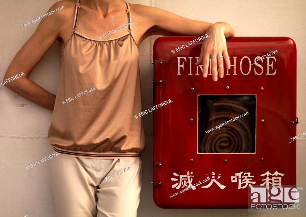 Stock Photo: Woman Standing On Fire Hose On A Ferry, Hong Kong, China.