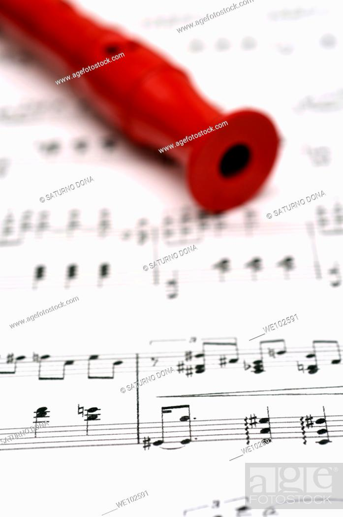 Stock Photo: red flute on music sheet.