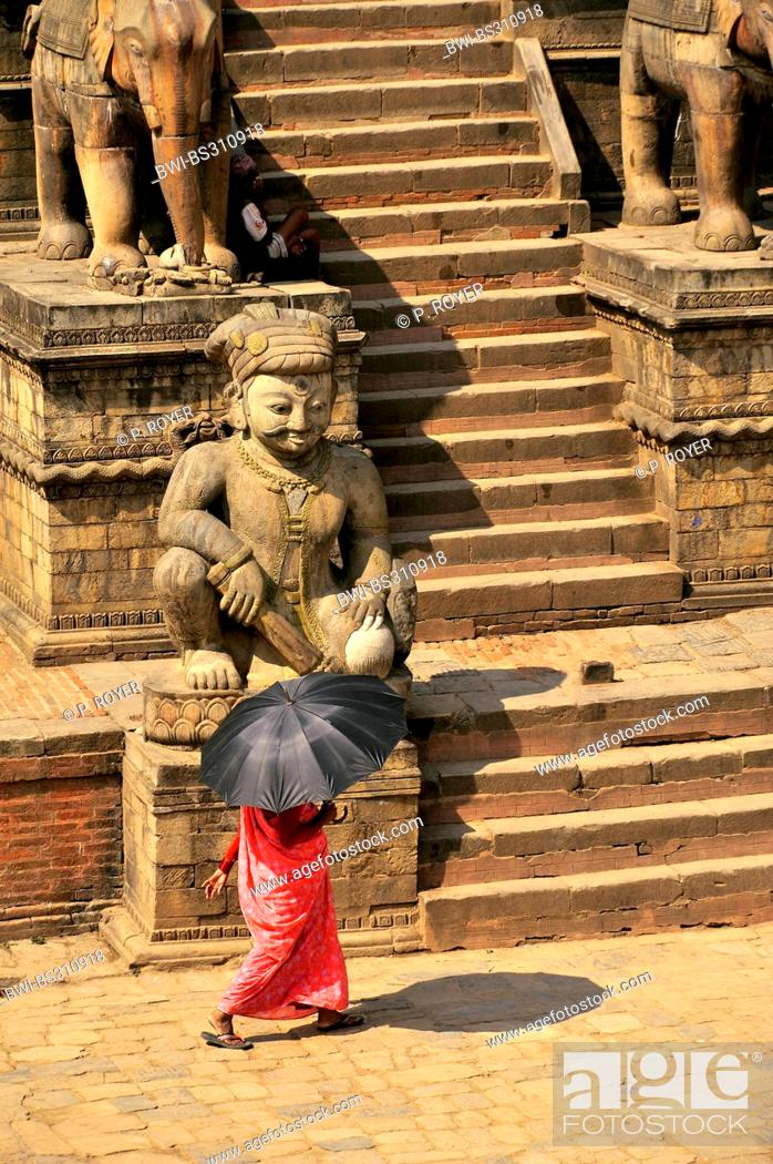 Imagen: woman with an umbrella serving as a sunshade crossing the Bhaktapur Durbar Square at the royal palace, Nepal, Bhaktapur.