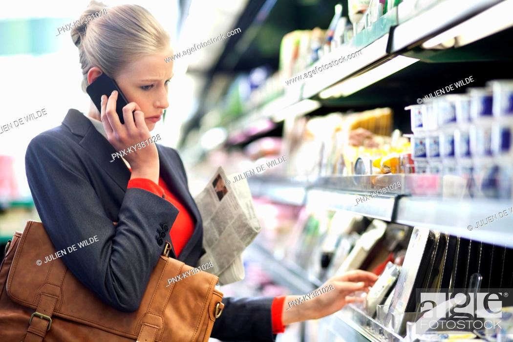 Stock Photo: Woman in a supermarket talking on a mobile phone.