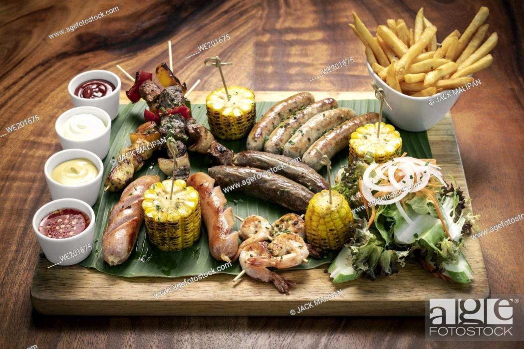 Stock Photo: organic mixed grill barbecue meat platter rustic set meal with sausages, skewers, side dishes and sauces.