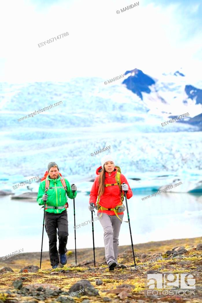 Stock Photo: Adventure hikers travel people walking with hiking poles on Iceland by glacier and glacial lagoon / lake of Fjallsarlon, Vatna glacier.