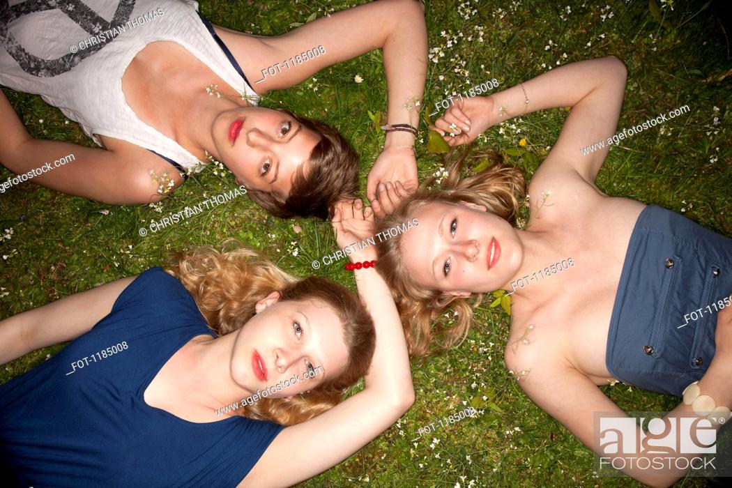 Stock Photo: Three female friends lying in the grass in a circle looking sensually at the camera.