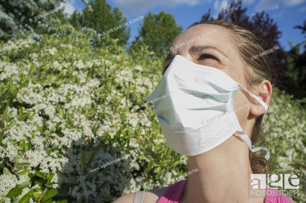 Imagen: Young woman with protective mask at blooming park with half-closed eyes because of the strong sun.