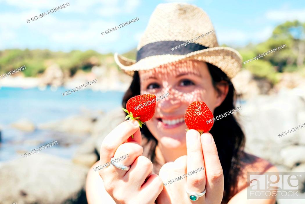 Stock Photo: Hands of woman on the beach holding strawberries.