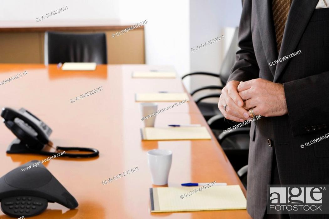 Stock Photo: Mid section view of a businessman standing in a conference room.