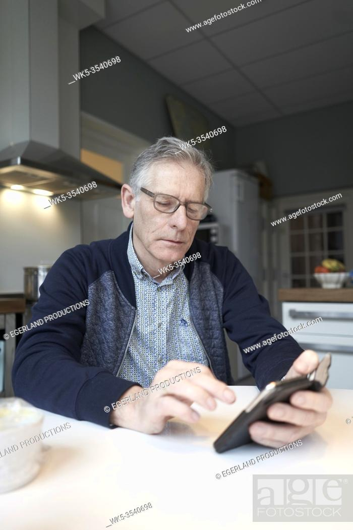 Stock Photo: senior man using smartphone at breakfast table in kitchen.