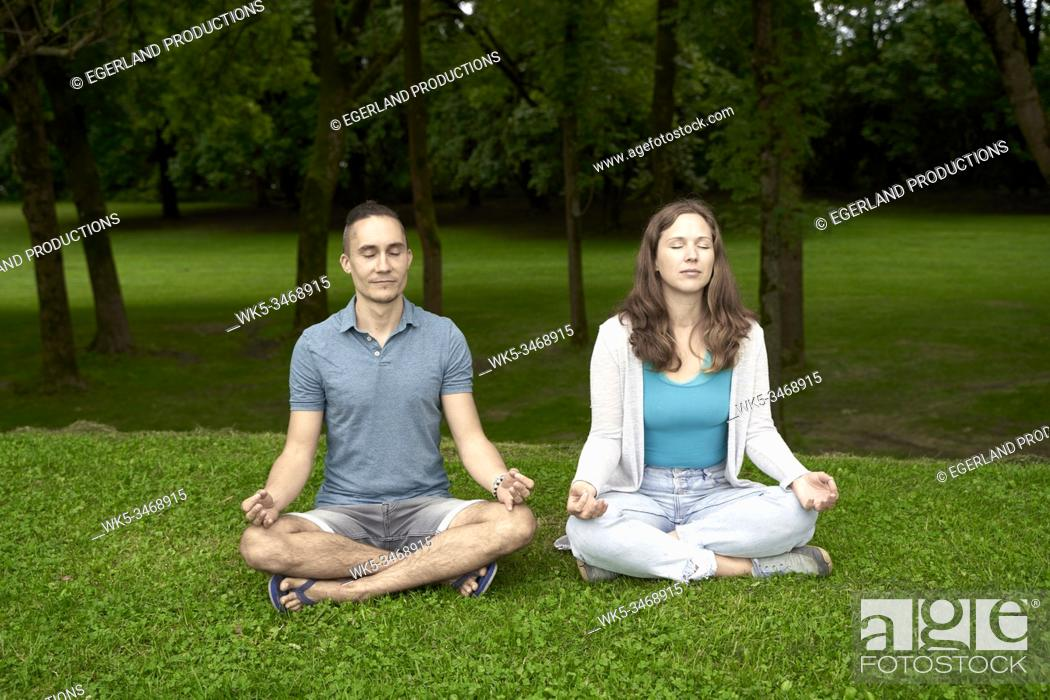 Stock Photo: Couple doing yoga in park. Munich, Germany.