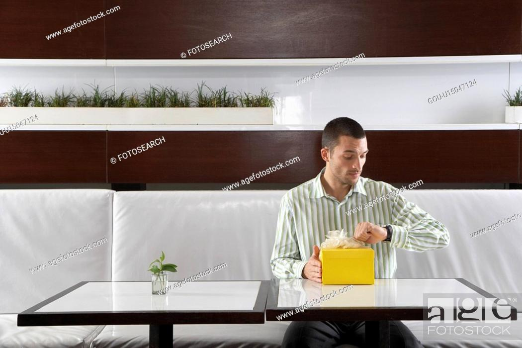 Stock Photo: Man with present checking the time in restaurant.