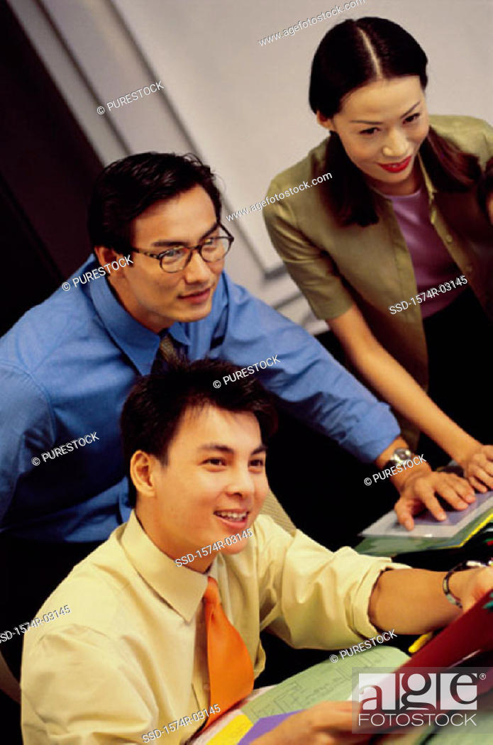 Stock Photo: Two businessmen and a businesswoman in an office.