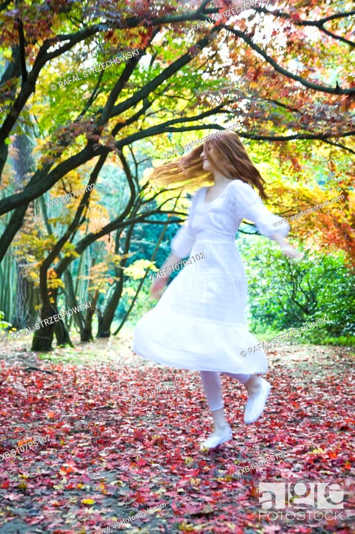 Stock Photo: Ginger woman dancing in park.