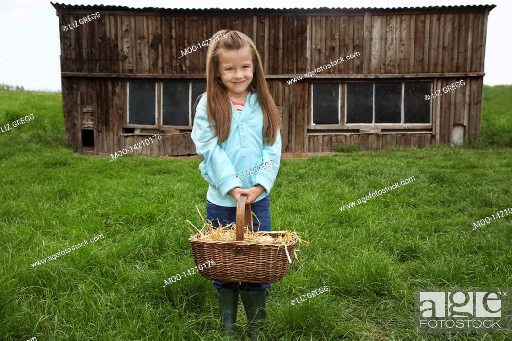 Stock Photo: Girl 5-6 holding egg basket at farm portrait.