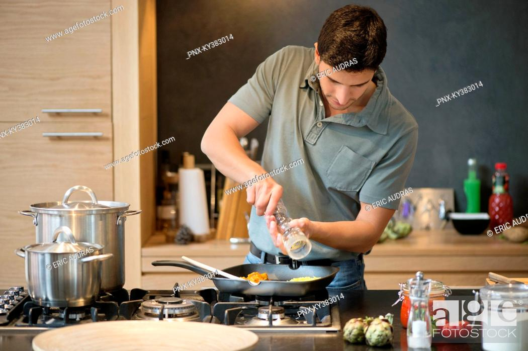 Stock Photo: Man preparing food in the kitchen.
