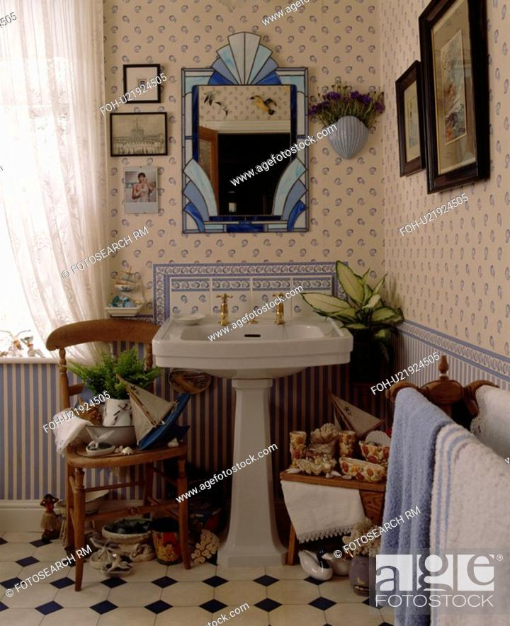 Stock Photo - Blue stained glass mirror above pedestal basin in seaside themed bathroom with blue+white wallpaper and dado