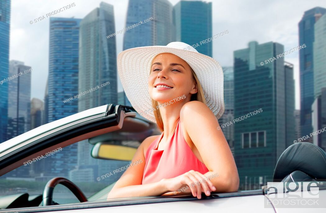 Stock Photo: woman in hat in convertible car over singapore.