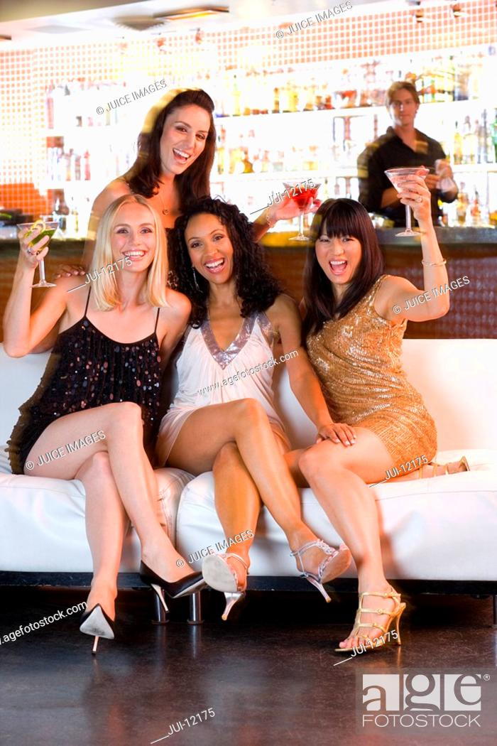 Stock Photo: Medium group of young women with drinks in bar, smiling, portrait.
