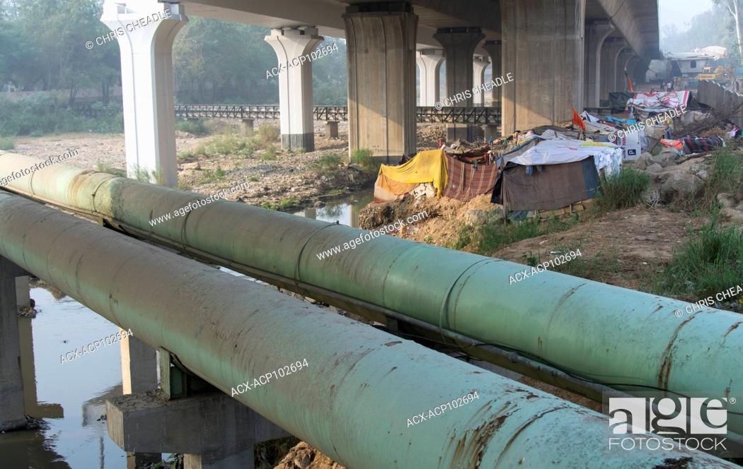 Stock Photo: Makeshift shanty housing under freeway, Delhi, India.