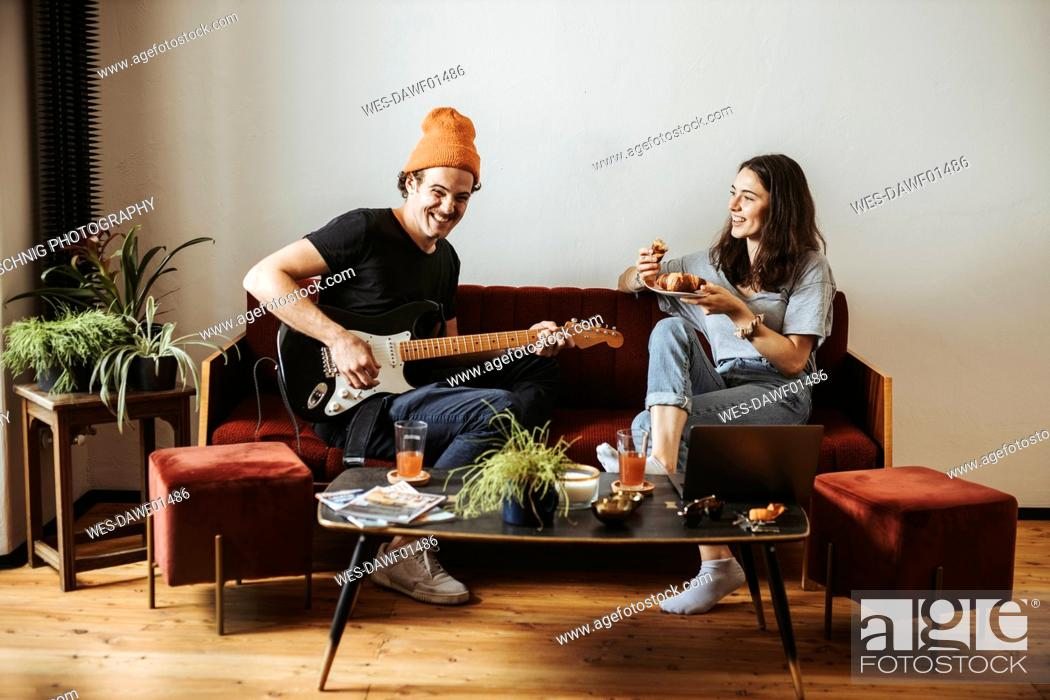 Imagen: Couple relaxing together on the couch at home.