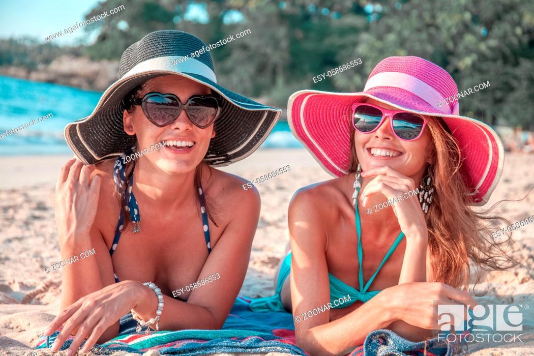 Stock Photo: Beautiful young women in sunhats laying on beach.