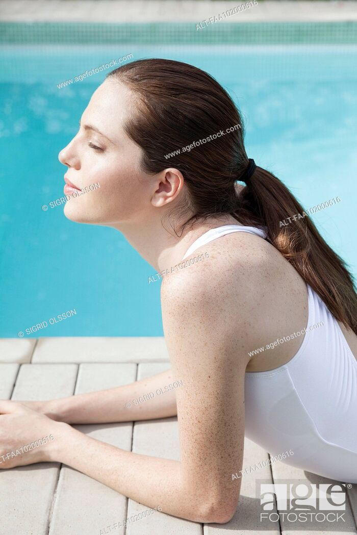 Stock Photo: Young woman sunbathing beside pool with eyes closed.