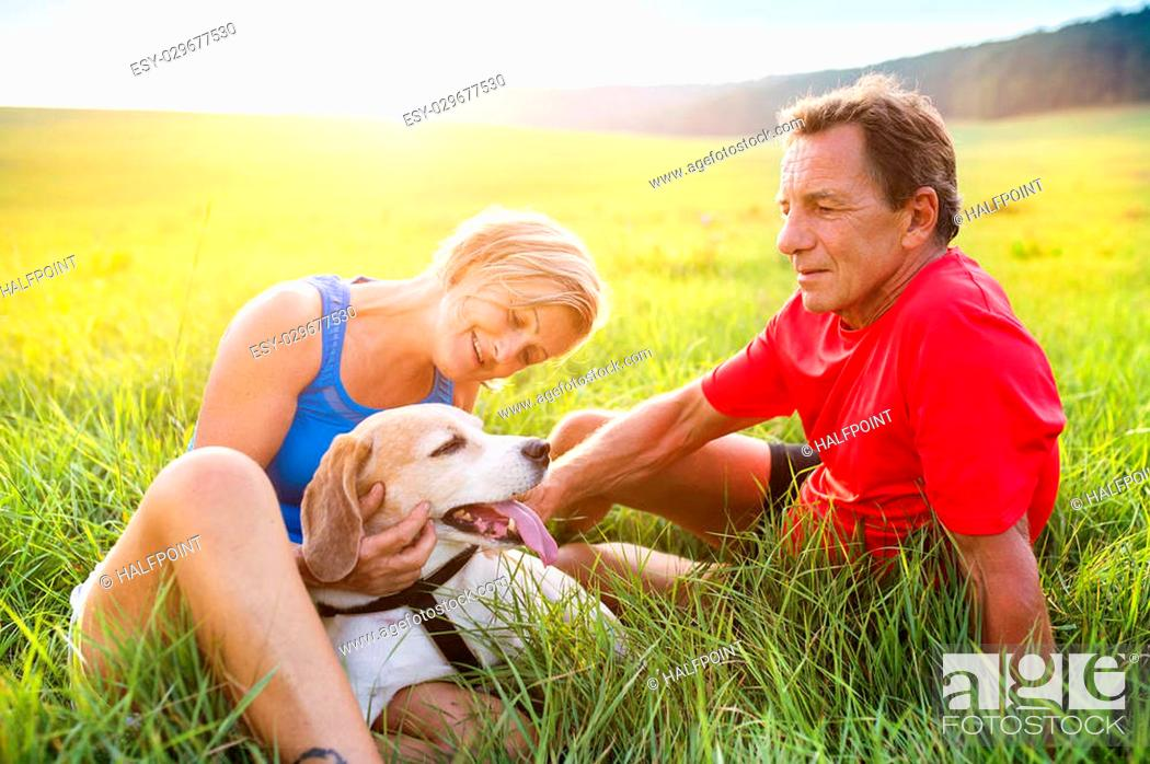 Stock Photo: Active seniors having a break during their run outside in green nature.