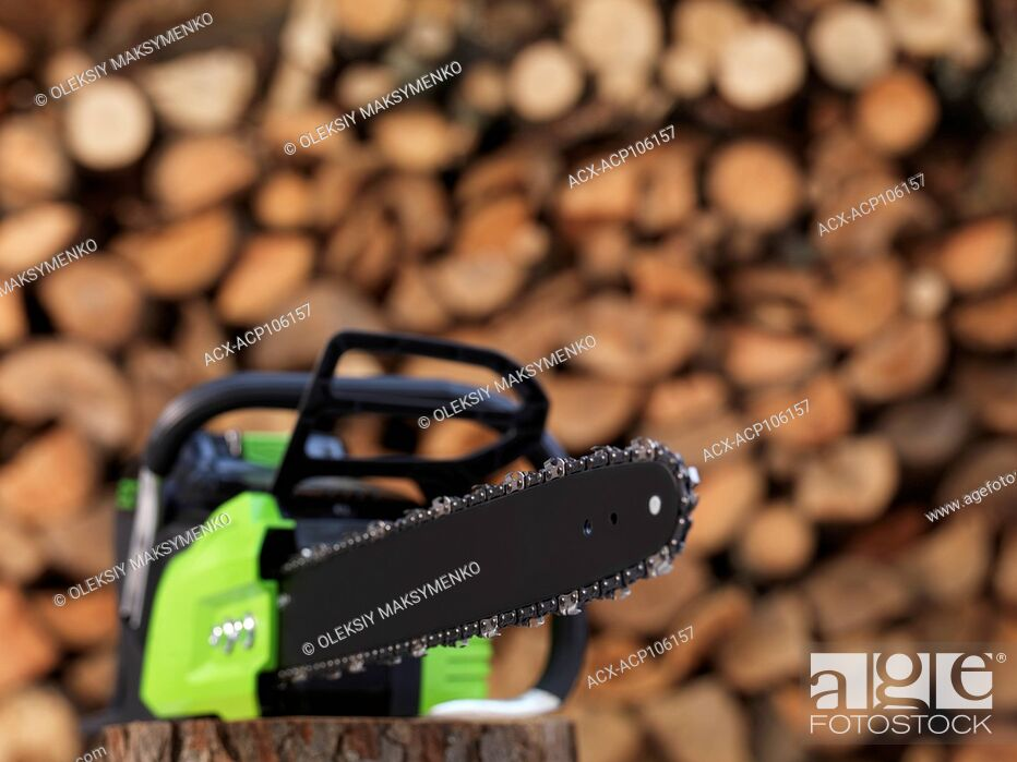 Stock Photo: Electric Cordless battery powered chainsaw in front of stacked firewood in the background.
